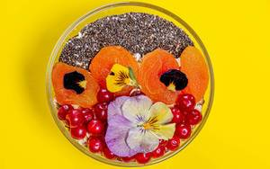 Obene Aufnahme von einer Schüssel mit Haferflocken, Beeren, Chiasamen und essbaren Blumen