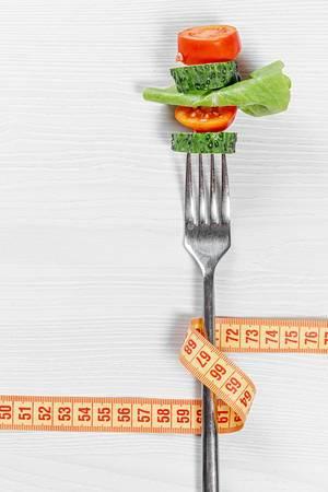Obene Aufnahme von einigen Stückchen Gemüse auf einer Gabel, eingewickelt durch einem Bandmaß als Symbol der gesunden Ernährung