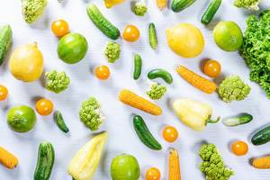 Obene Aufnahme von grünem und gelbem Obst und Gemüse auf weißem Holztisch