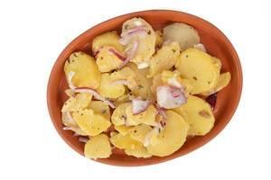 Obene Aufnahme von Kartoffelsalat mit geschnittenen Zwiebeln
