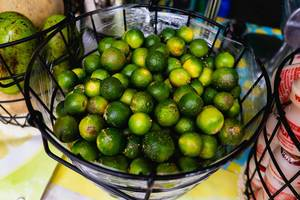Obene Aufnahme von Philippinischen Zitronen bekannt als Calamansi in einem Metallkorb