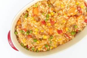 Obene Aufnahme von Risotto mit Erbsen, Mais, Tomaten, Karotten und Paprika