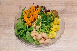 Obene Aufnahme von veganem Salat mit Edamame, Blumenkohl, Spinat, Rote Beete, Zucchini und Pilze