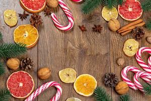 Obene Aufnahme von Weihnachtslutscher mit getrockneten Zitrusfrüchten und Tannenzweigen auf einem Holztisch