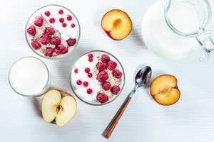 Obene Aufnahme von zwei Schalen mit frischem Haferflocken und Beeren neben einer Glas Milch und frischem Obst auf weißem Holztisch