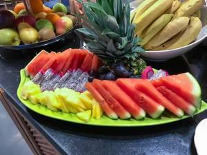 Obstteller mit Wassermelone, Ananas, Drachenfrucht und Trauben