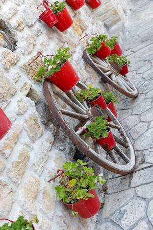 Ochsenkarren-Räder mit roten Blumentöpfen