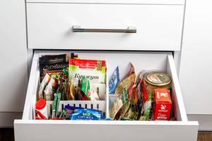 Offene Küchenschublade mit verschiedenen Gewürzen und Kräutern