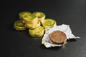 Offene Schoko-Münze mit golden-silbernem Papier, neben einem Münzstapel auf dunklem Untergrund