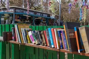 Öffentliche Bücherei zum Tauschen und Mitnehmen auf einem Regalbrett an einem grünen Gartenzaun im spanischen Barceloneta Park in Barcelona