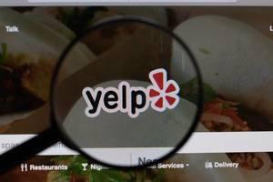 """Offizielles """"Yelp"""" Logo und Schriftzug, vergrößert durch ein Lupenglas dargestellt"""