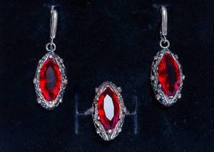 Ohrringe und Fingerring aus Silber mit rotem Rubin vor schwarzem Hintergrund