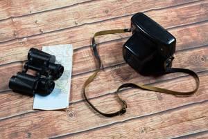 Old camera and binoculars on wooden floor