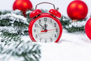 Old-fashioned red alarm clock in winter setting with artificial snow and Christmas decoration