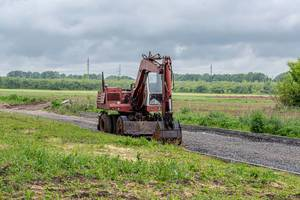 Old red excavator on the road in the field