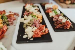 Oliven, Schinken, Käse, Wurst und getrocknete Tomaten auf einem schwarzen Brett auf dekoriertem Tisch