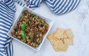 Oliven-Tapenade neben Keks-Crackern, auf einem Marmortisch