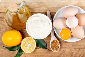 Olivenöl, frische Zitronen, Senf-Samen, Eier und frische Mayonnaise auf einem Holz Hintergrund - Draufsicht
