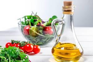 Olivenöl in Karaffe vor Zutaten für einen gesunden Salat, in einer Glasschale auf einem Holztisch