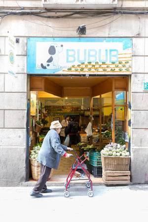 Oma mit Rollator passiert den spanischen Gemüsehändler Bubub an der Carrer de Joaquín Costa Fußgängerzone in Barcelona, Spanien