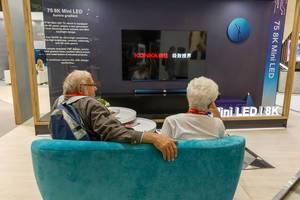 Oma und Opa auf der Couch: Altes Pärchen sitzt beim Messebesuch auf dem Sofa, vor einem 75 8K Mini LED Fernseher von Konka