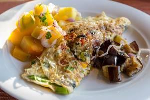 Omelette mit Mangosalat und Auberginen auf weißem Teller