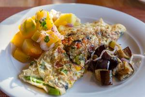 Omelette with Mango fruit salad and eggplants on white plate