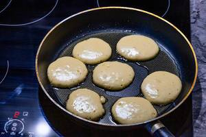 On the electronic cooking surface fried pancakes in a frying pan (Flip 2019)