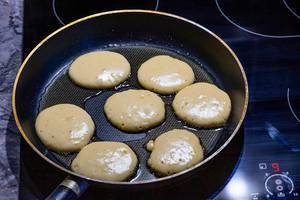 On the electronic cooking surface fried pancakes in a frying pan