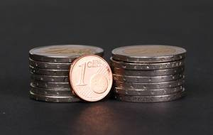 One Euro cent coin placed in front of piles of coins