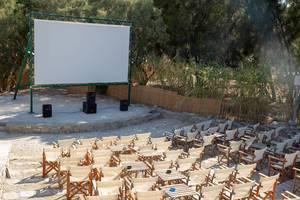 """Open-Air Freiluftkino """"Cinema Enastron"""", mit Holzstühlen und Tischen, im Park auf Paros, Griechenland"""