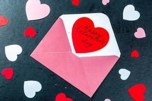 Open envelope with a red card-heart and wishes of happy Valentine
