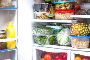 Open Fridge filled up with groceries such as Mustard, Lettuce, Beans, Pineapple, Tomatoes, Apple and Avocados
