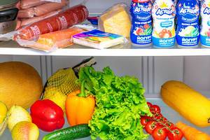 Open fridge with fresh vegetables, fruits and other products inside