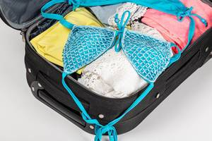 Open suitcase with beach or summer clothes