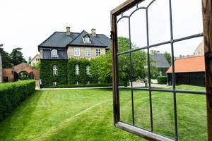 Open window looking out to a green grass field and elegant Danish house