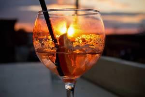 Orange Abenddämmerung hinter einem alkoholischen Drink im Longdrinkglas