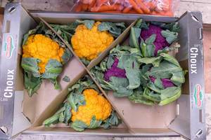 Orange and violet cauliflower in a vegetable crate at Timeout Market Lisbon