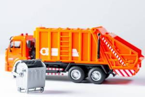 Orange garbage truck toy on a white background
