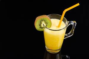 Orange juice with Kiwi in the glass on the black background