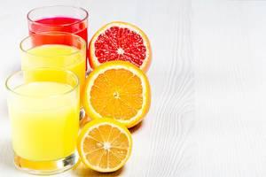 Orange, lemon and grapefruit fresh juices on a white wooden background (Flip 2019)