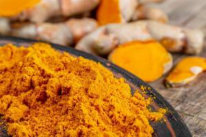 Orange turmeric powder with fresh turmeric