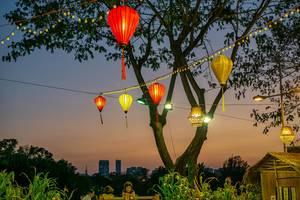Orange und gelbe Papierlaternen vor Himmel zum Sonnenuntergang nahe Crescent Lake in Saigon, Vietnam