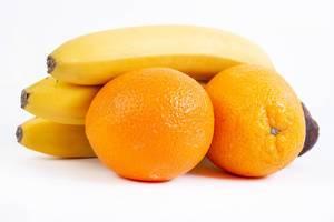 Orangenfrüchte und Bananen, isoliert auf weißem Hintergrund