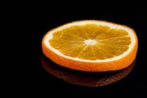 Orangenscheibe auf einer schwarzen, reflektierenden Oberfläche