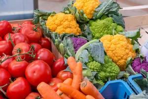 Oranger und violetter Blumenkohl, Romanesco, Karotten Schalotten und Tomaten am Timeout Market in Lissabon