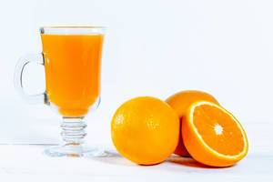Oranges and a glass of juice on a white background
