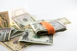 Oranges Geldband hält gefalteten Stapel aus Dollarnoten auf verteilten US-Dollarscheinen