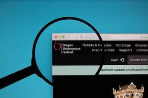 Oregon Shakespeare Festival logo on a computer screen with a magnifying glass