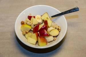 Organic vanilla chia porridge with apples, bananas and various nuts in white bowl
